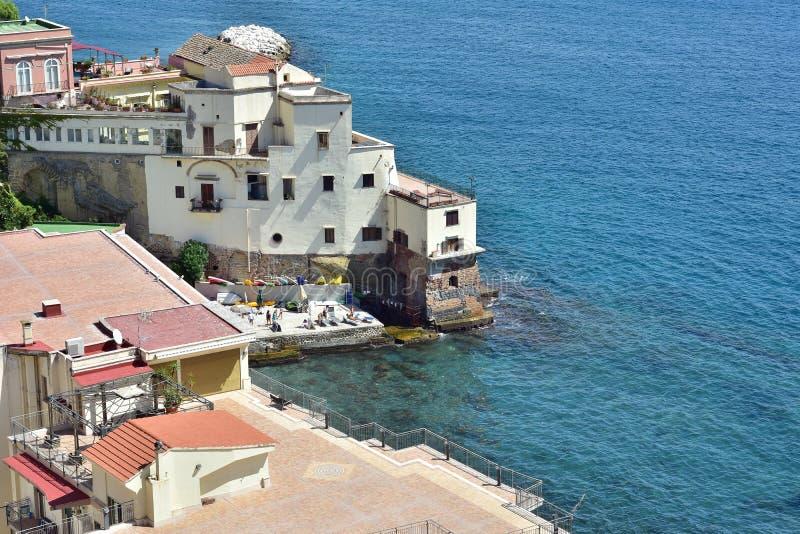 Terrace houses on rocky coast. Mediterranean terrace houses build on steep rocky cliffs along rugged coast right above blue sea surface stock photos