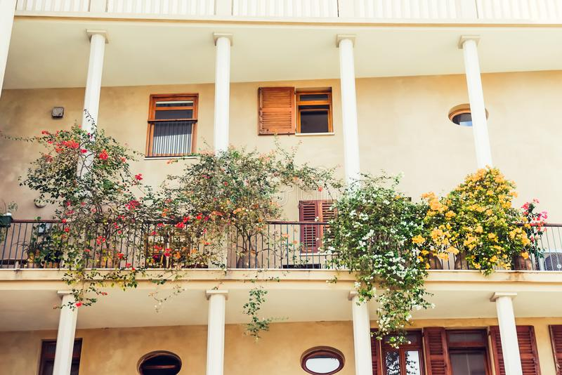 Mediterranean Two-storid building with columns and open balcony with flowering trees in pots, summer terrace with potted plant nea royalty free stock photo