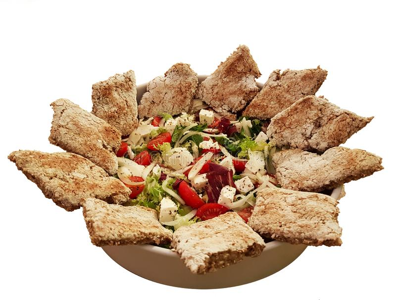 Mediterranean vegetable salad with smooth slices of homemade bread, spread out around the edge of the plate. Veggirarian dish on a royalty free stock image