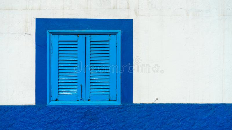 Mediterranean white washed house with blue wooden window shutters royalty free stock photography