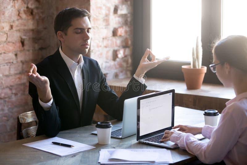 Meditieren am Arbeitsplatz vor Laptop stockfotos
