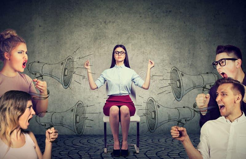 Meditierende Geschäftsfrau, die keine Aufmerksamkeit auf Menge von schreienden verärgerten Leuten lenkt lizenzfreie stockfotos