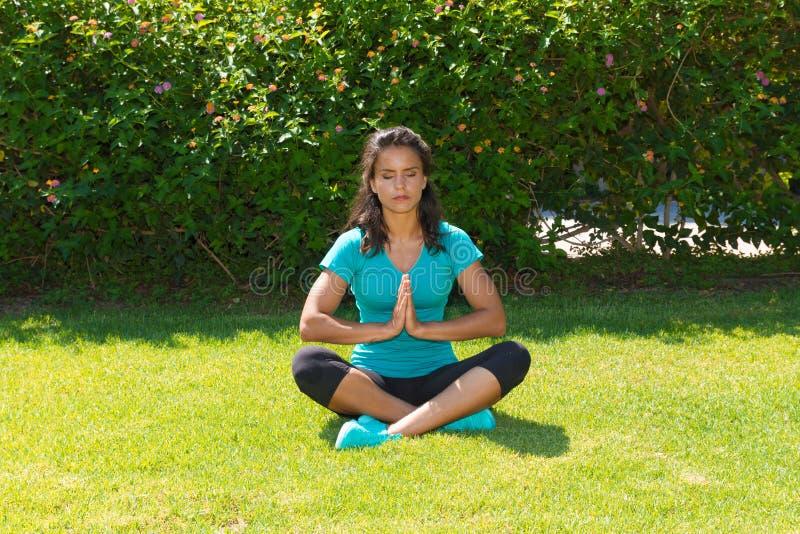 Meditierende junge Frau in der Lotoshaltung, an gesetzt stockfotos