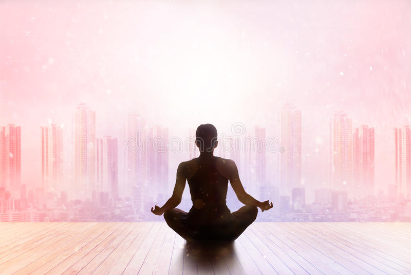 Meditierender bunter Pastell der Frau auf Stadtsonnenuntergangrückseite stockfotos