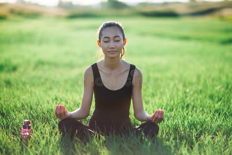 Meditierendes Sitzen der Asiatin auf Gras lizenzfreie stockbilder