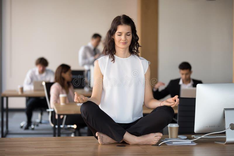 Meditierendes Sitzen des barfüßigangestellten in Lotussitz auf Büro stockbild