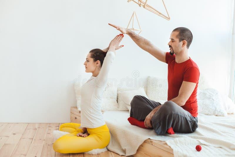 Meditierendes Yoga des jungen Mannes und der Frau lizenzfreies stockbild