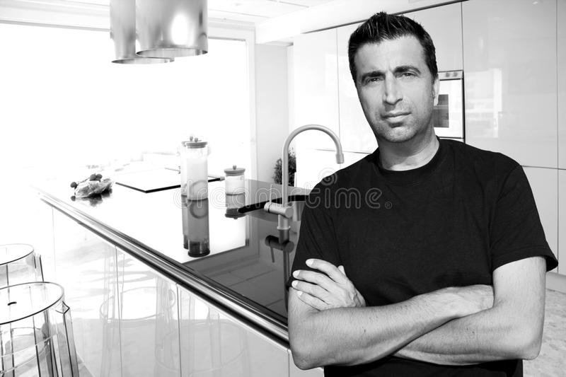 Medium age man in modern kitchen interior portrait stock photo
