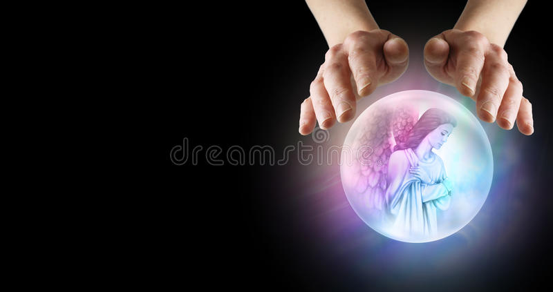 Medium with Angel Helper. Pair of hands hovering over crystal ball showing Angel with arms crossed over chest on a wide black background banner stock images