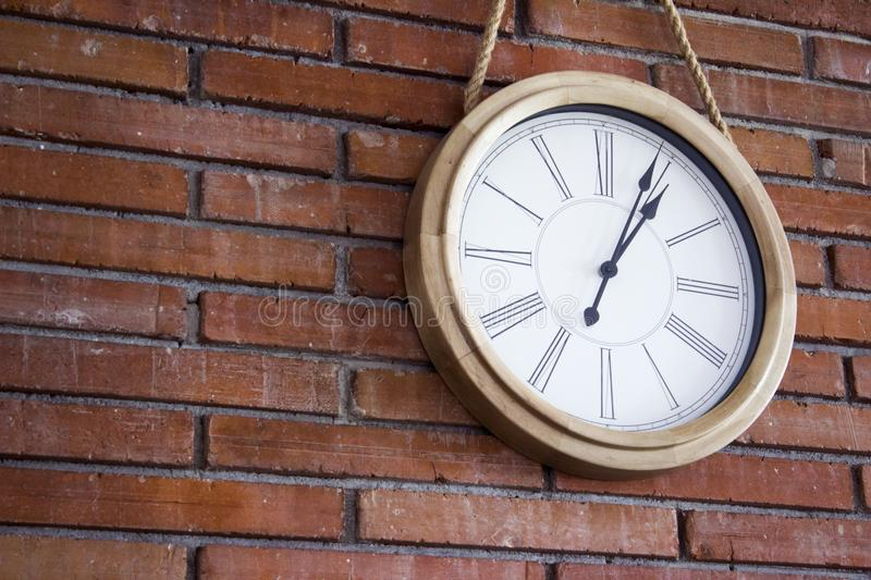 Medium close shot of a wooden wall clock with roman numerals hanging in a red brick wall. stock photos