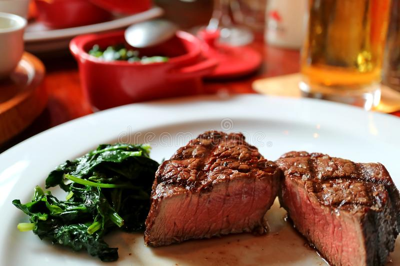 Medium grilled tenderloin steak cut in half with sauteed spinach on white plate royalty free stock photo