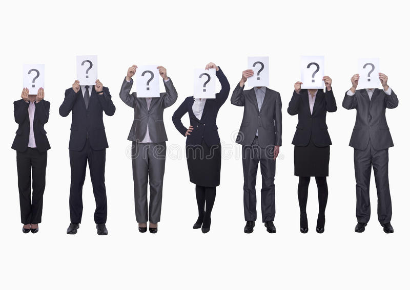 Medium group of business people in a row holding up paper with question mark, obscured face, studio shot royalty free stock image