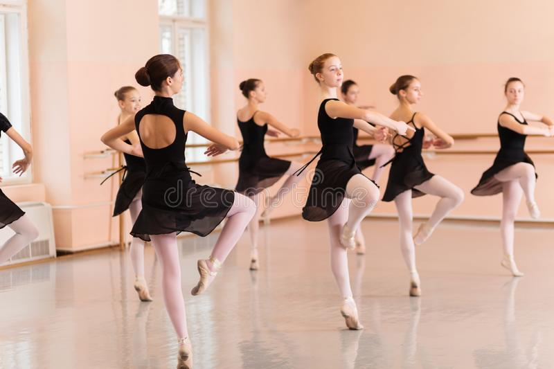 Medium group of teenage girls in black dresses practicing ballet moves in a large dance studio royalty free stock photography