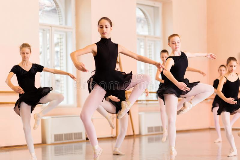 Medium group of teenage girls practicing Pas de Chat jump. Medium group of teenage girls in black dresses practicing Pas de Chat jump in dancing studio stock images