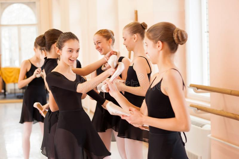 Medium group of teenage girls having fun and relaxing after ballet class. In a large dancing studio stock photos