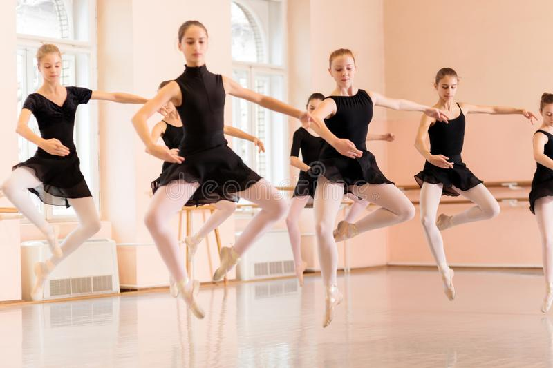 Medium group of teenage girls practicing ballet moves in a large dancing studio royalty free stock image