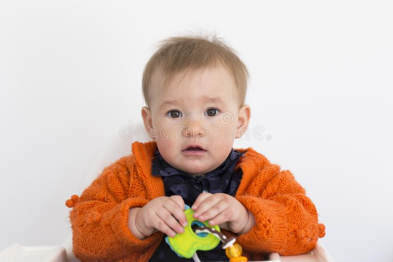 Medium horizontal shot of adorable fair toddler girl sitting in high chair holding colourful toy royalty free stock photo