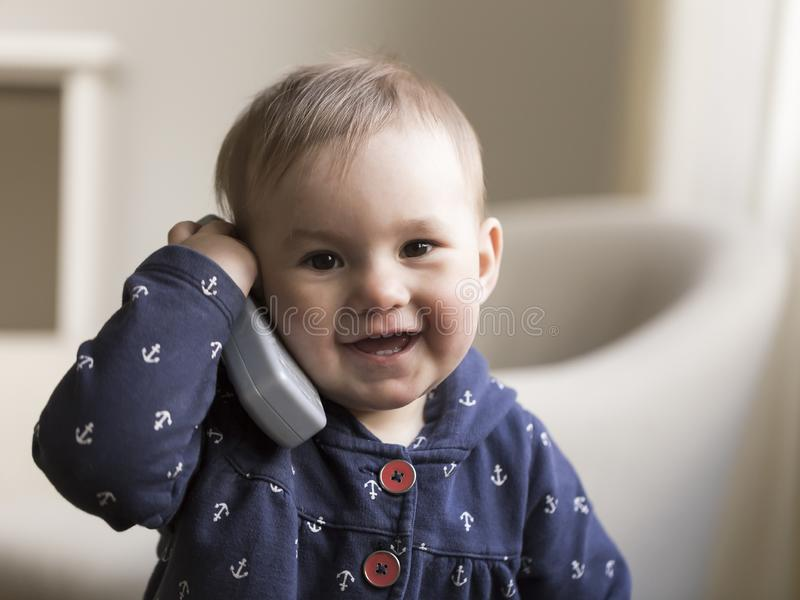 Medium horizontal shot of fair smiling toddler girl holding a toy phone receiver to her ear. Medium horizontal shot of fair smiling toddler girl in navy jacket royalty free stock images