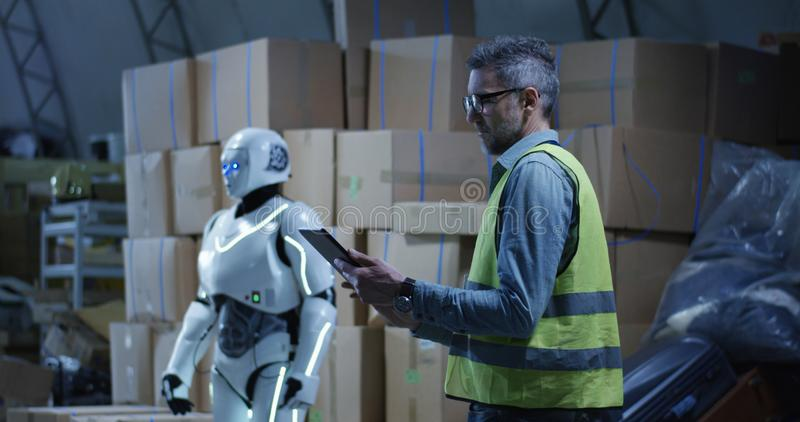 Man watching robot working in a warehouse. Medium long shot of a man using a tablet while watching a robot working in a warehouse stock photo