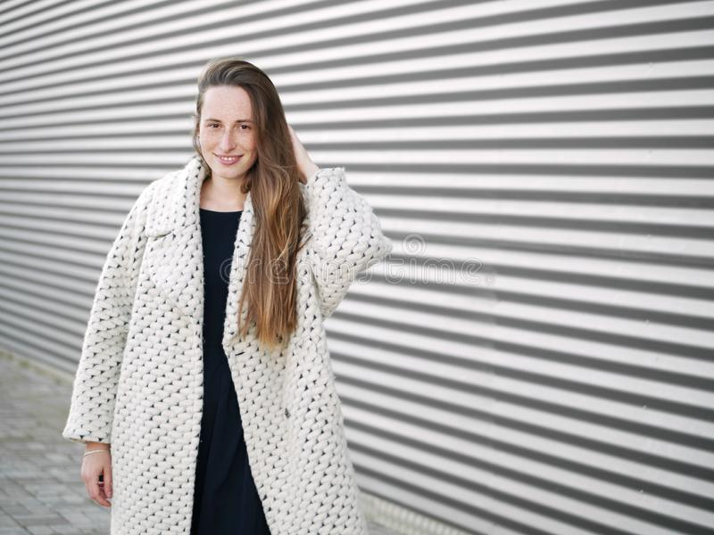 Medium long shot of young trendy dressed serious caucasian woman posing outdoor on urban city blurred geometric background cold stock photos
