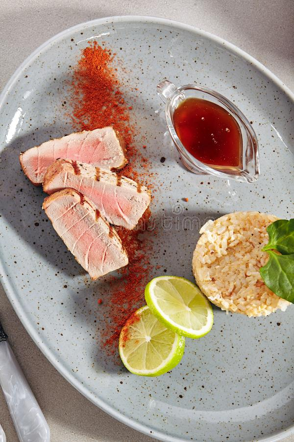 Medium Rare Ahi Tuna Steak with Red Spices Powder, Rice and Lime Top View royalty free stock image