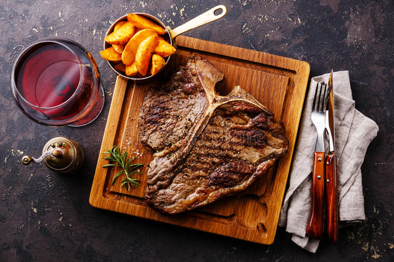 Medium rare Grilled T-Bone Steak with potato wedges. And wine on serving board block on dark background stock photo
