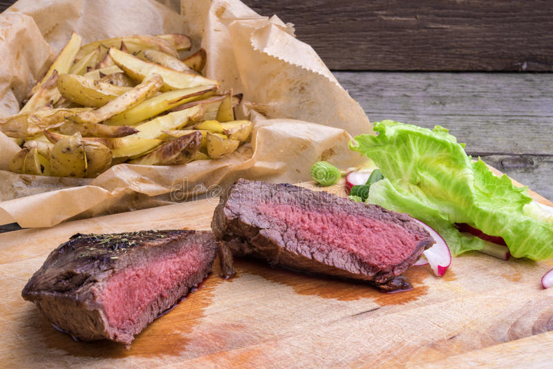 Medium rare grilled top rump steak with roasted potatoes and sal. Medium rare grilled top rump steak seasoned with green pepper and thyme, served on a wooden royalty free stock photos