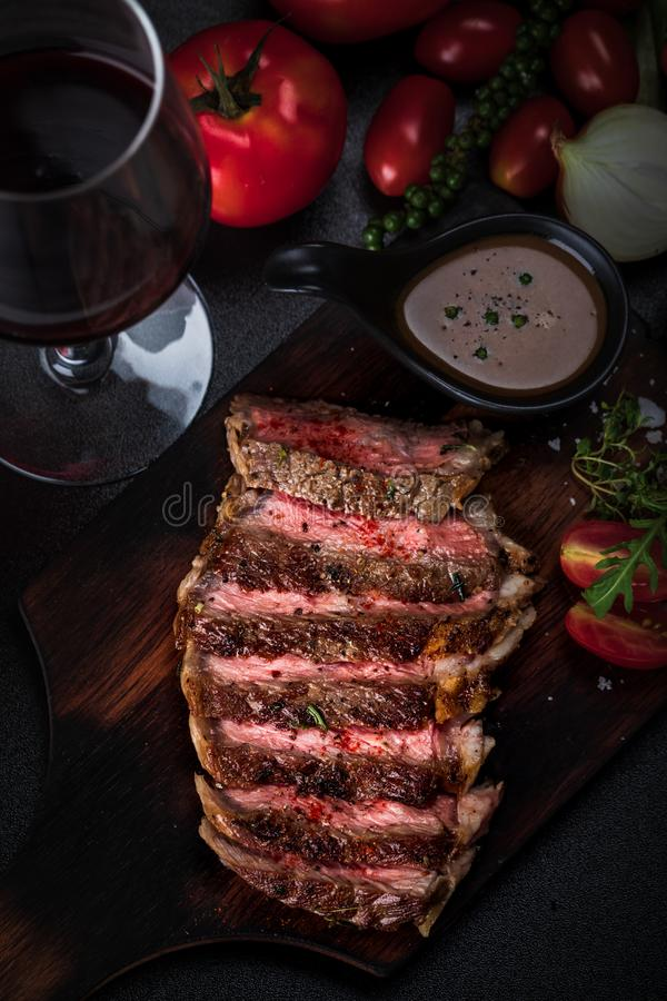 Medium rare meat rib eye steak slices in pan on chopping wooden royalty free stock images