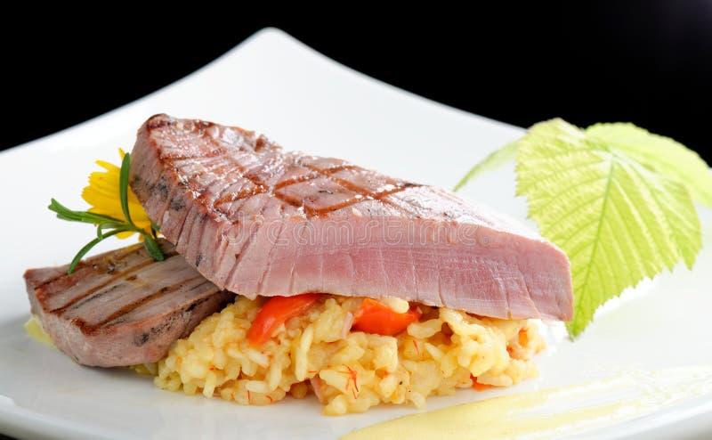 Medium rare sashimi tuna steak. On saffron risotto stock photo
