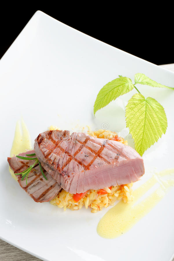 Medium rare sashimi tuna steak. On saffron risotto royalty free stock photos