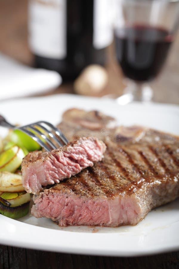 Medium rare steak on the plate. Medium rare T-bone steak with roasted leek and red wine stock photos