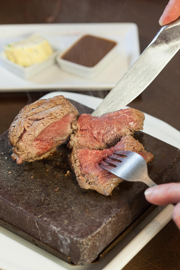 Medium rare steak sizzling on hot stone plate being sliced royalty free stock photos