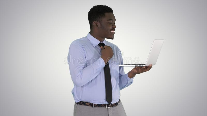 Cheerful successful young African American manager with laptop having video conference call with business partners on. Medium shot. Cheerful successful young royalty free stock photography
