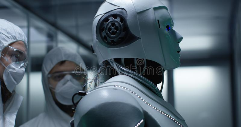 Engineer fixing wires on robot control stock photography