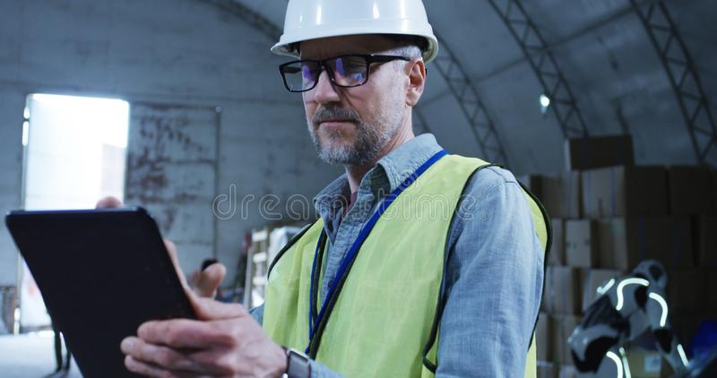 Engineer supervising a robot in a warehouse. Medium shot of engineer supervising a robot in a warehouse stock images