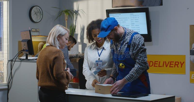 Customer receiving package at a customer service desk. Medium shot of a female customer receiving a package at a customer service desk royalty free stock photos