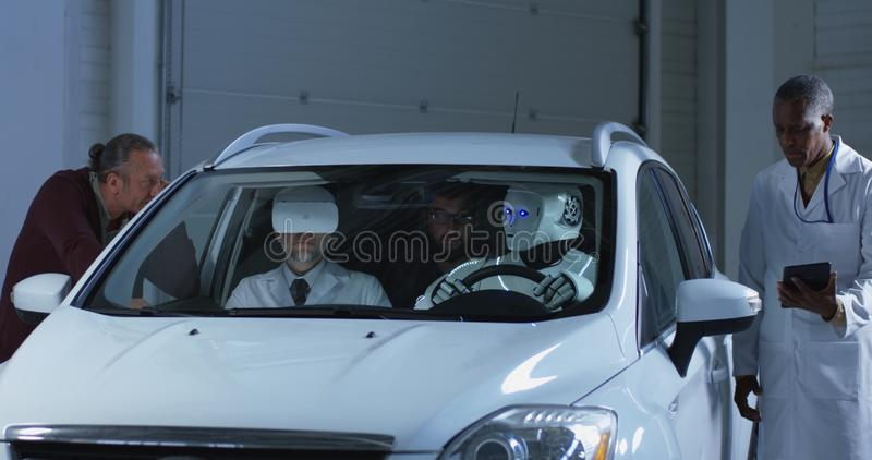 Scientists testing a car driving robot royalty free stock image