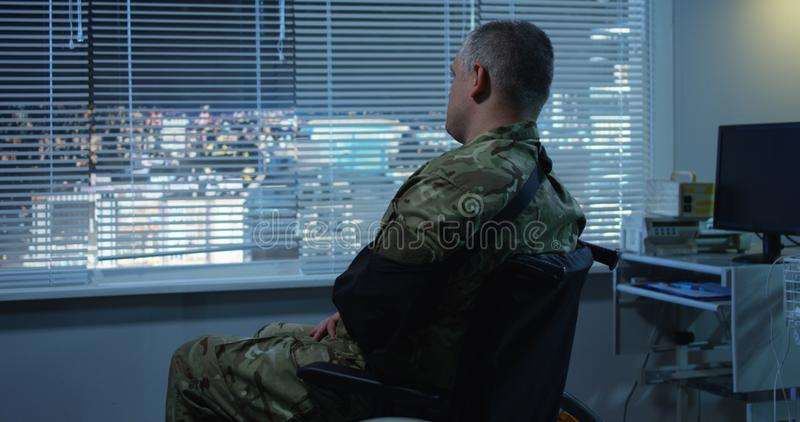 Soldier sitting in wheelchair in hospital. Medium shot of injured soldier sitting in wheelchair and looking through window in hospital room stock photo