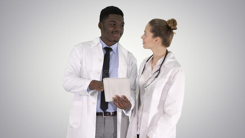 Intellectual healthcare professional afro american doctor with collegue using digital tablet on gradient background. royalty free stock photos