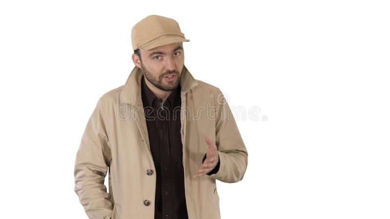 A positive bearded male dressed in a trench coat walking and talking on white background. royalty free stock photos