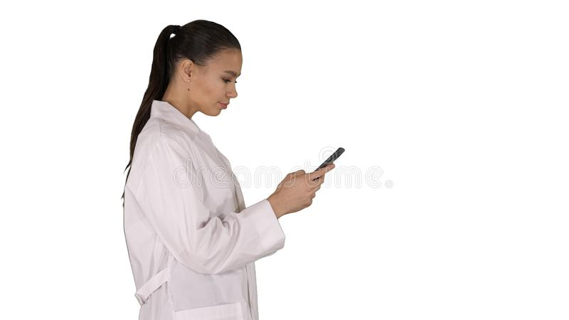 Cheerful cute young woman doctor typing text on phone while walking on white background. Medium shot. Side view. Cheerful cute young woman doctor typing text on stock photos