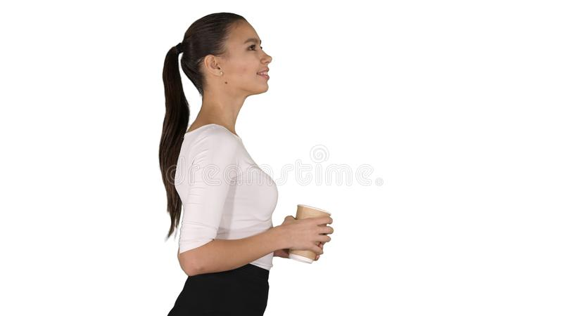 Relaxed stylish businesswoman drinking coffee walking on white background. royalty free stock images