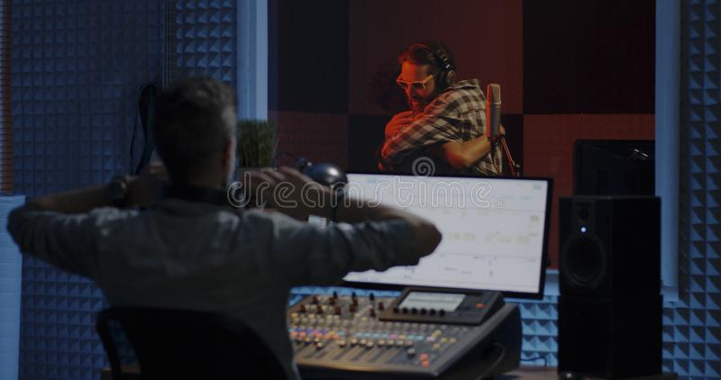 Singers and sound engineer working in studio. Medium shot of singers completing recording session in a studio stock photography