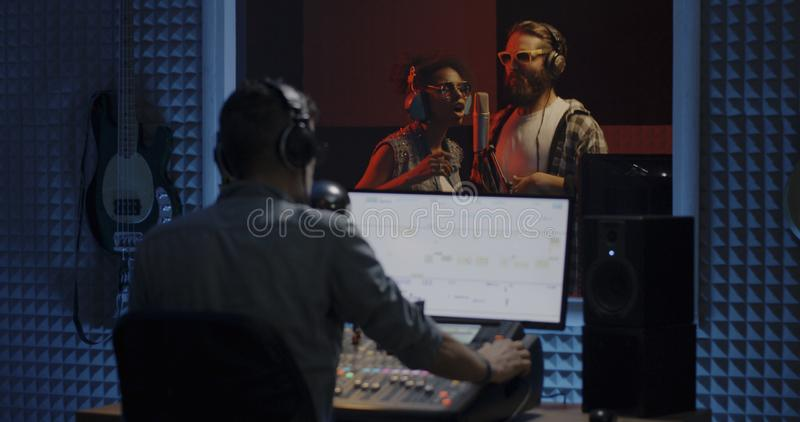 Singers and sound engineer working in studio. Medium shot of singers and sound engineer working in studio royalty free stock photo