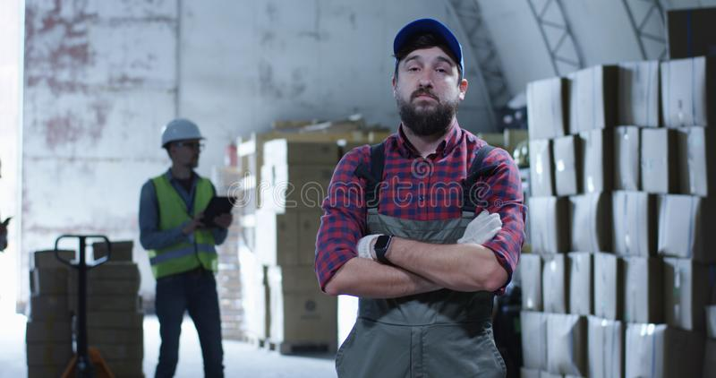 Worker smiling at camera in a warehouse. Medium shot of worker smiling at camera in a warehouse royalty free stock photo