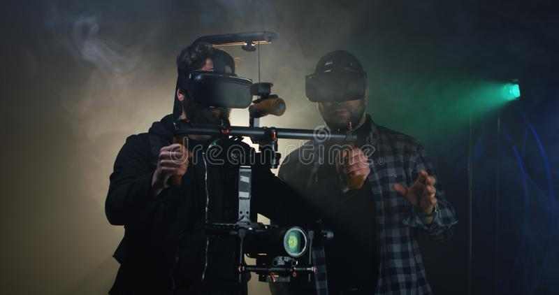 Director instructing a cameraman on a film set. Medium shot of a young director instructing the steadicam using cameraman on a film set stock images