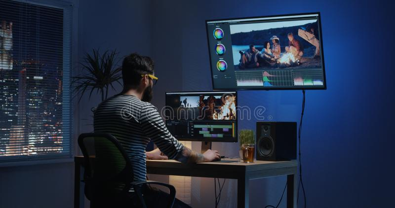 Young man sitting back and editing video inside a room. Medium shot of a young men sitting back and editing a video inside a modern video studio royalty free stock photo