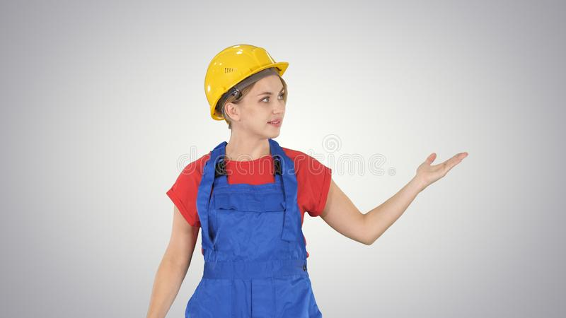Young smiling worker woman talking and showing objects to her sides on gradient background. royalty free stock photos