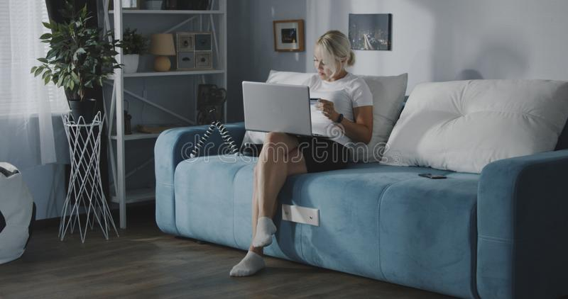 Woman shopping online with laptop. Medium shot of a young woman shopping online with laptop while sitting on a sofa at home royalty free stock photo