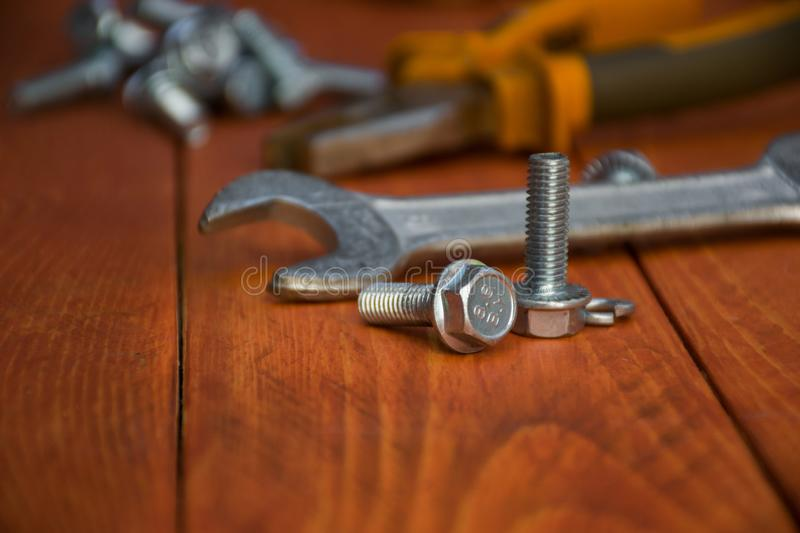 Bolt emphasis . Closeup of a wrench with bolts on a wooden table. Medium size wrench with metal bolts, close, in the background, flat-nose pliers. bolt emphasis royalty free stock photos